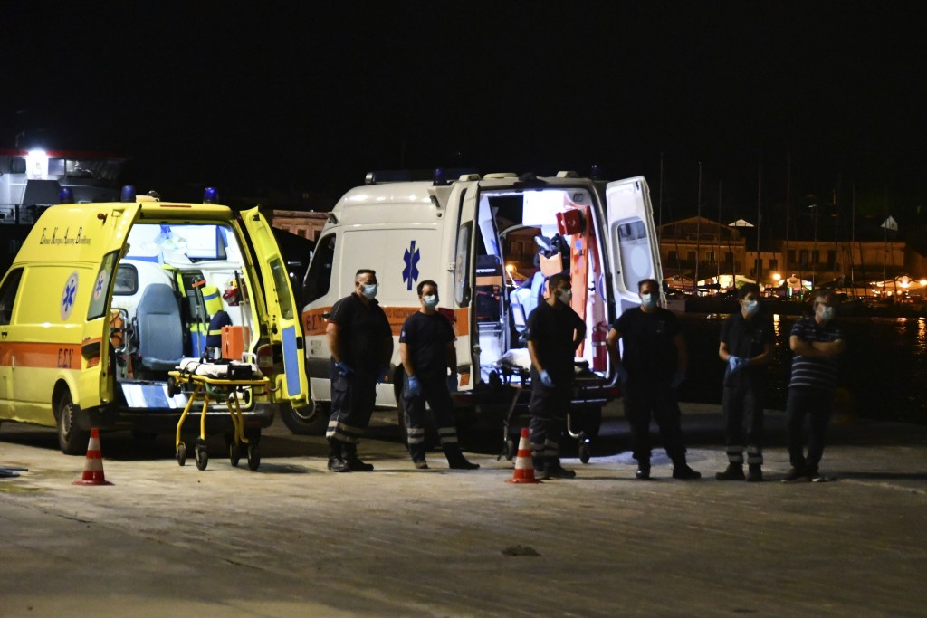 Paramedics wait next to ambulances at Pythagorio port, on the eastern Aegean island of Samos, Greece, late Monday, Sept. 13, 2021. Authorities in Gree...