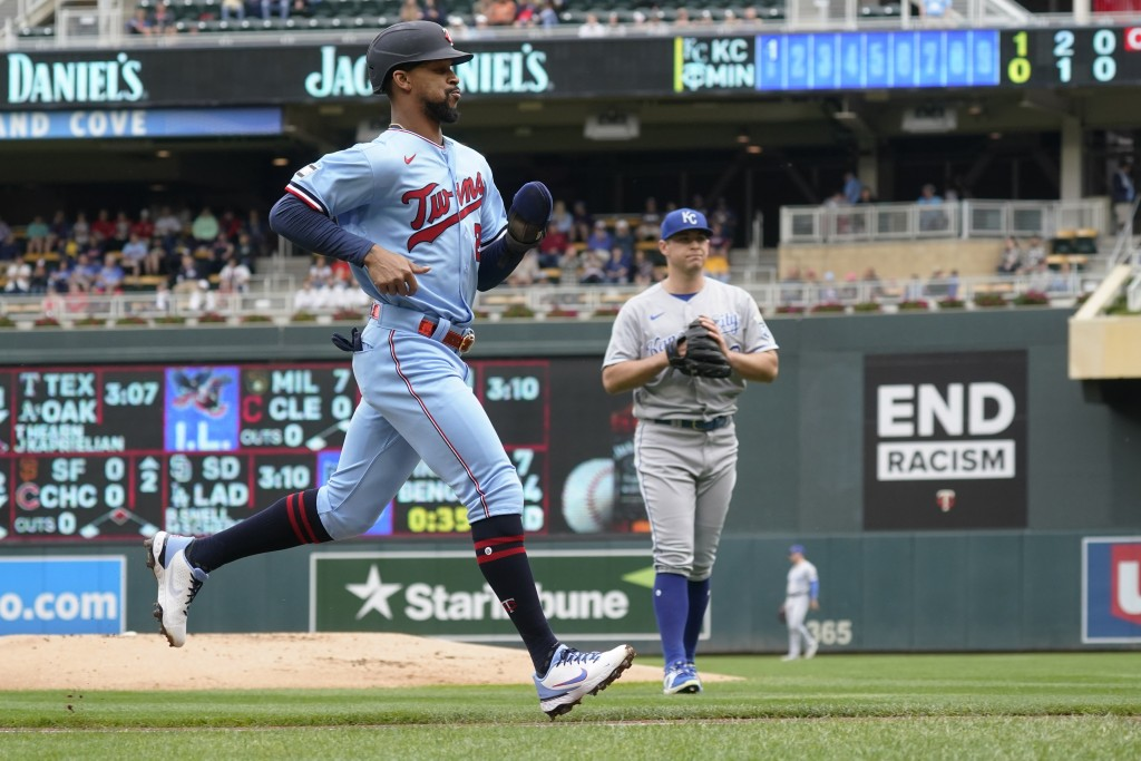 Minnesota Twins' Byron Buxton, left, jogs home on a sacrifice fly by Luis Arraez off Kansas City Royals pitcher Kris Bubic, right, in the first inning...