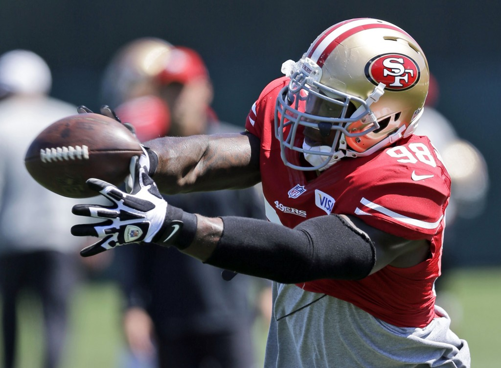 FILE - In this Aug. 12, 2013, file photo, San Francisco 49ers linebacker Parys Haralson reaches for the ball during NFL football training camp in Sant...