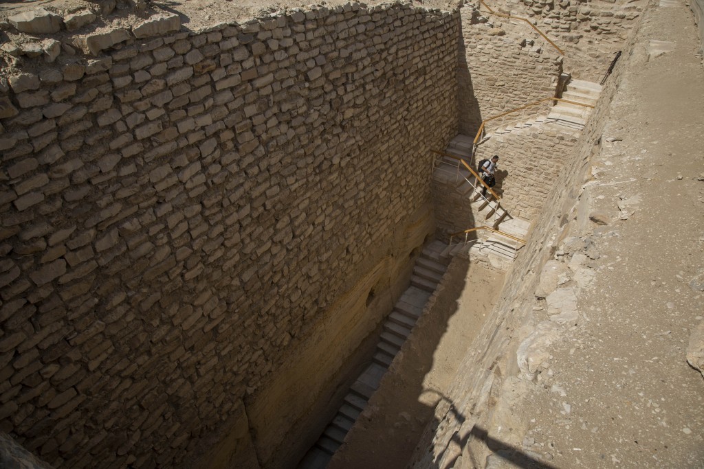 A journalist walks down stairs towards the southern cemetery of King Djoser, to film it after its restoration, near the famed Step Pyramid, in Saqqara...
