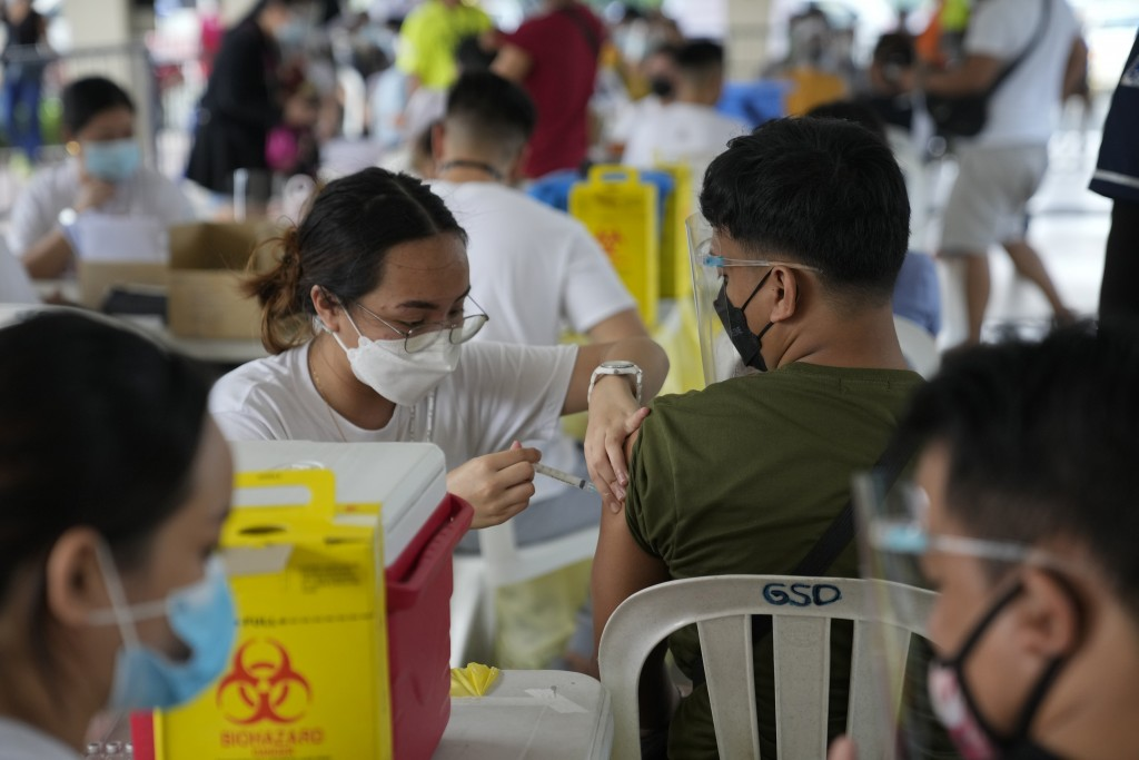 A man is inoculated with China's Sinovac COVID-19 vaccine in Quezon city, Philippines on Monday, Sept. 13, 2021. The government continues to urge Fili...
