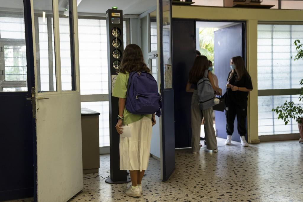 Α student checks her temperature as she arrives at a junior high school in Athens, Monday, Sept. 13, 2021. Public and private sector employees will ha...