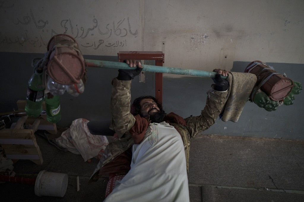 A Taliban fighter lifts a makeshift weight left behind by former prisoners at an empty area of the Pul-e-Charkhi prison in Kabul, Afghanistan, Monday,...
