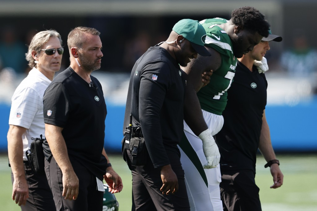 New York Jets offensive tackle Mekhi Becton is helped off the field during the second half of an NFL football game against the Carolina Panthers Sunda...