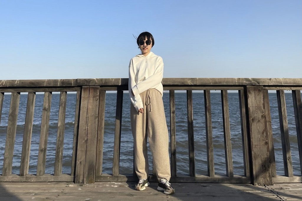 In this April 3, 2021, photo and released by Monica Ma, Monica Ma poses for a photo along the coast of Qinhuangdao in northern China's Hebei province....