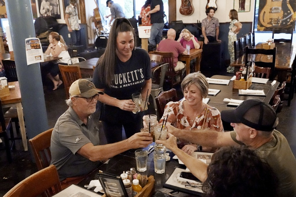 Macy Norman, center, serves a table of guests at Puckett's Grocery and Restaurant, Friday, Sept. 10, 2021, in Nashville, Tenn. In Nashville, tourism h...