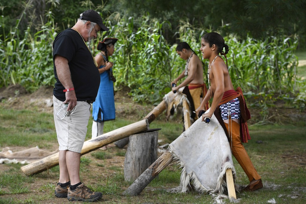 William Small Ear Coyote of Grafton, Mass., and a member of the Nipmuc Nation, right, talks with Joseph Soares of Acadia, R.I., left, as he demonstrat...