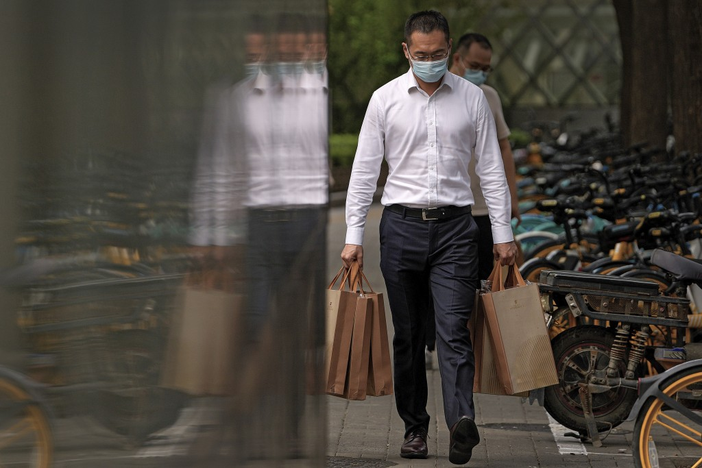 A man wearing a face mask to help protect from the coronavirus carries goody bags as he walks by a row of bicycles parked along a pavement in Beijing,...