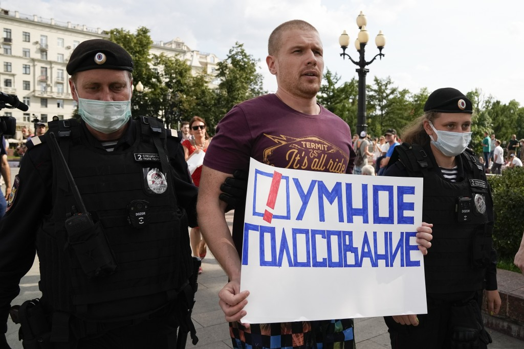 FILE - In this Aug. 14, 2021, file photo, Russian police detain an opposition activist with a poster reading Smart Voting during an anti-vaccination p...