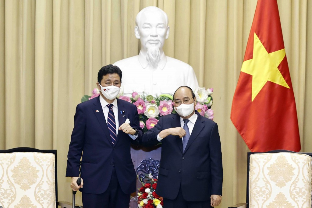 Vietnamese President Nguyen Xuan Phuc, right, and Japanese Defense Minister Nobuo Kishi stand for photo in Hanoi, Vietnam  Sunday, Sept. 12, 2021. Jap...