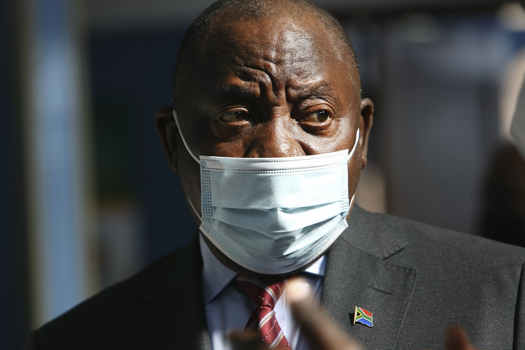 FILE — In this Thursday, July 29, 2021 file photo South African President Cyril Ramaphosa visits a COVID-19 vaccination centre in Tembisa, South Afric...