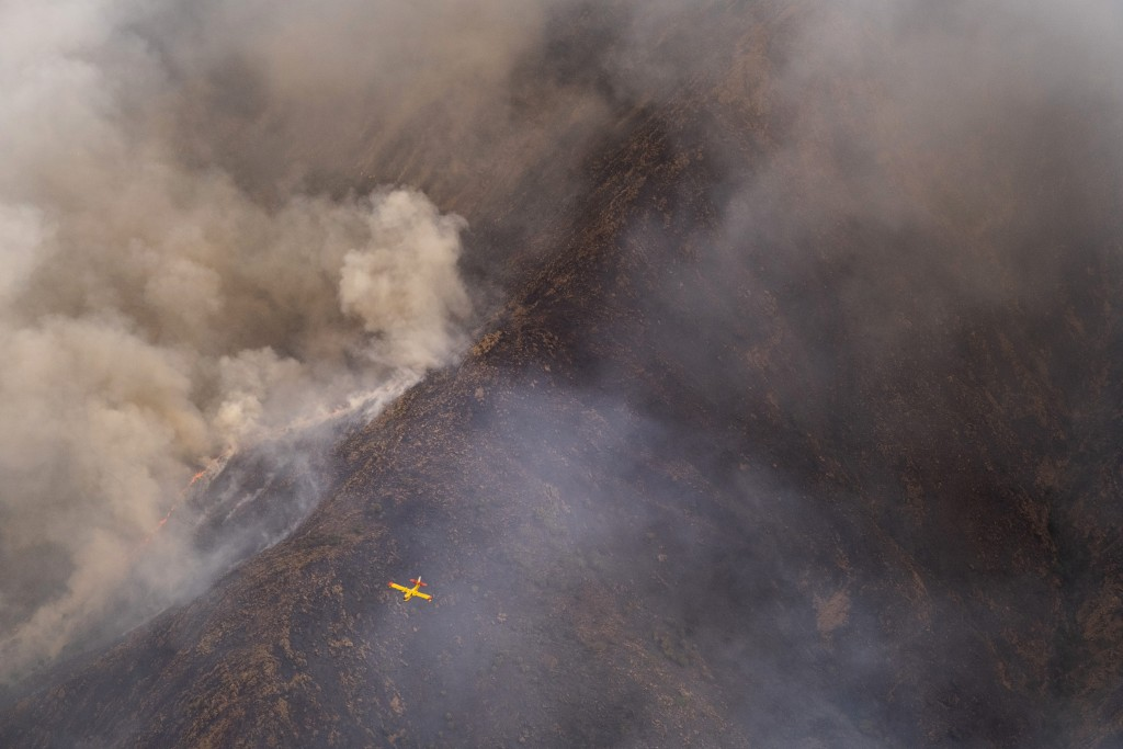 A seaplane flies over a wildfire near the town of Jubrique, in Malaga province, Spain, Monday, Sept. 13, 2021. Firefighting crews in southern Spain ar...