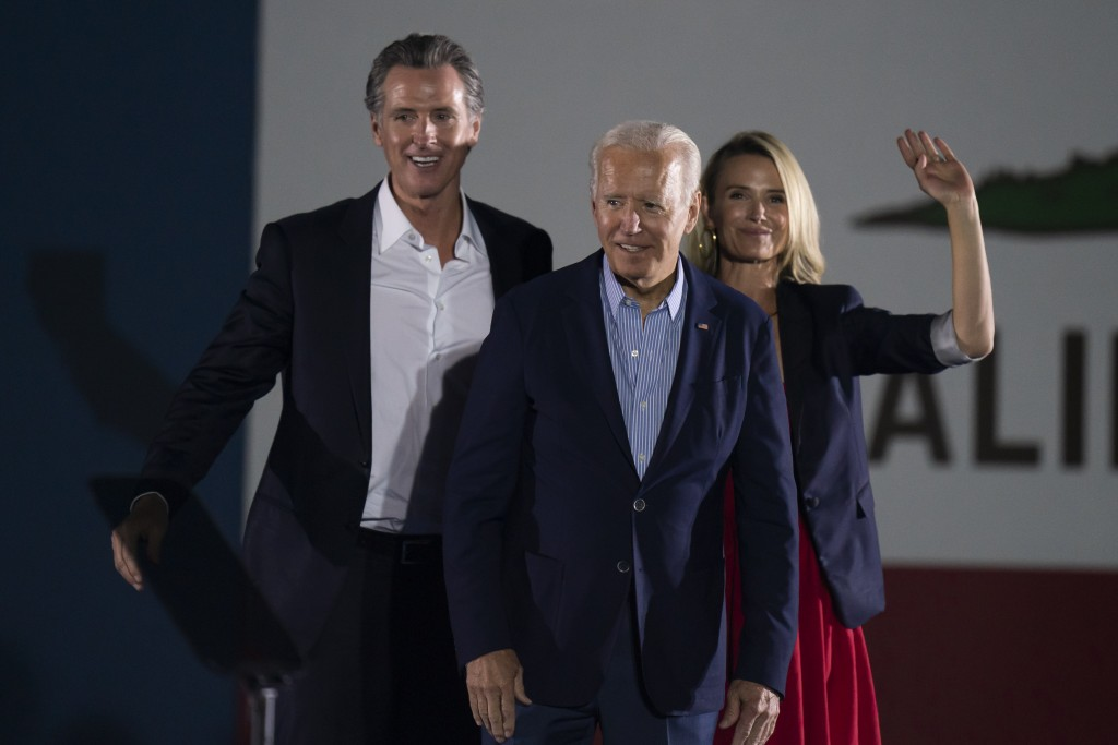 President Joe Biden, center, smiles to the crowd as he is flanked by California Gov. Gavin Newsom, and wife, Jennifer Siebel Newsom, at a rally ahead ...