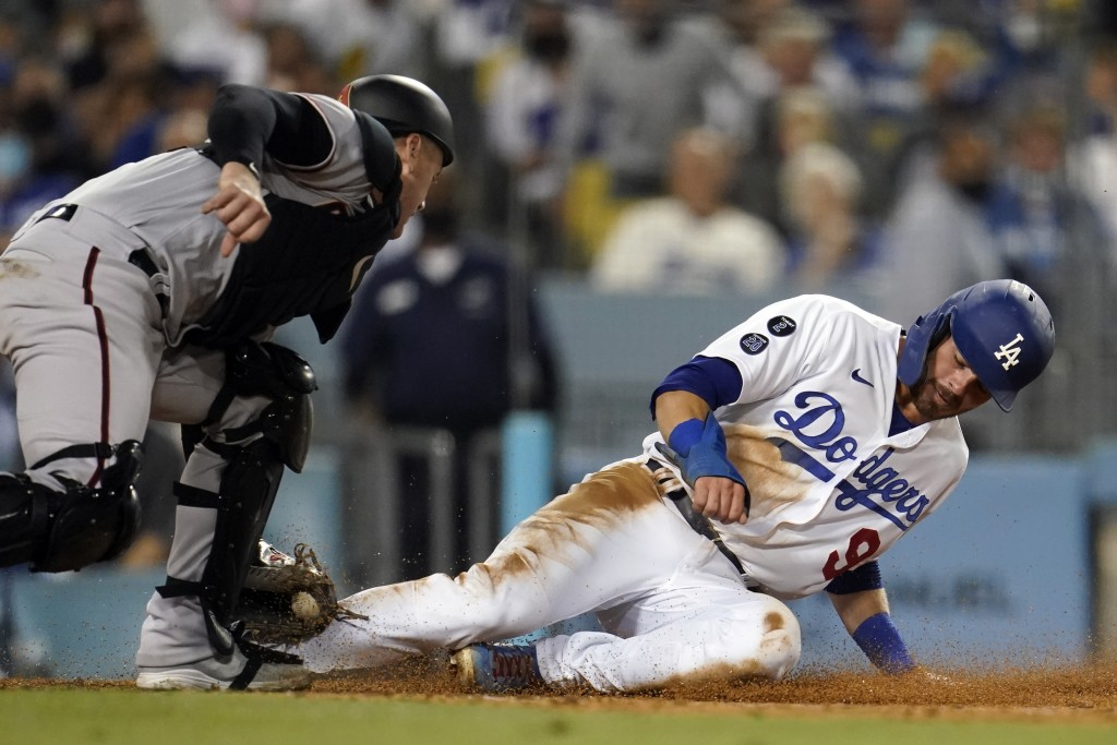 Los Angeles Dodgers' Gavin Lux, right, is tagged out at home plate by Arizona Diamondbacks catcher Carson Kelly after a sacrifice fly by Mookie Betts ...