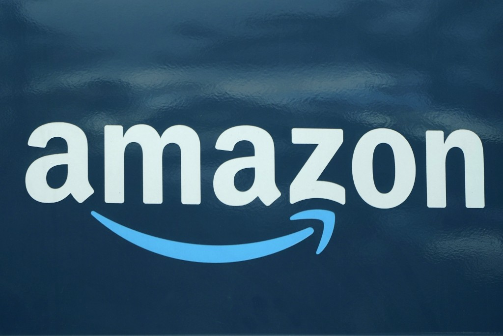 FILE - In this Oct. 1, 2020, file photo, an Amazon logo appears on an Amazon delivery van in Boston. Amazon says it is bringing its palm-recognition t...