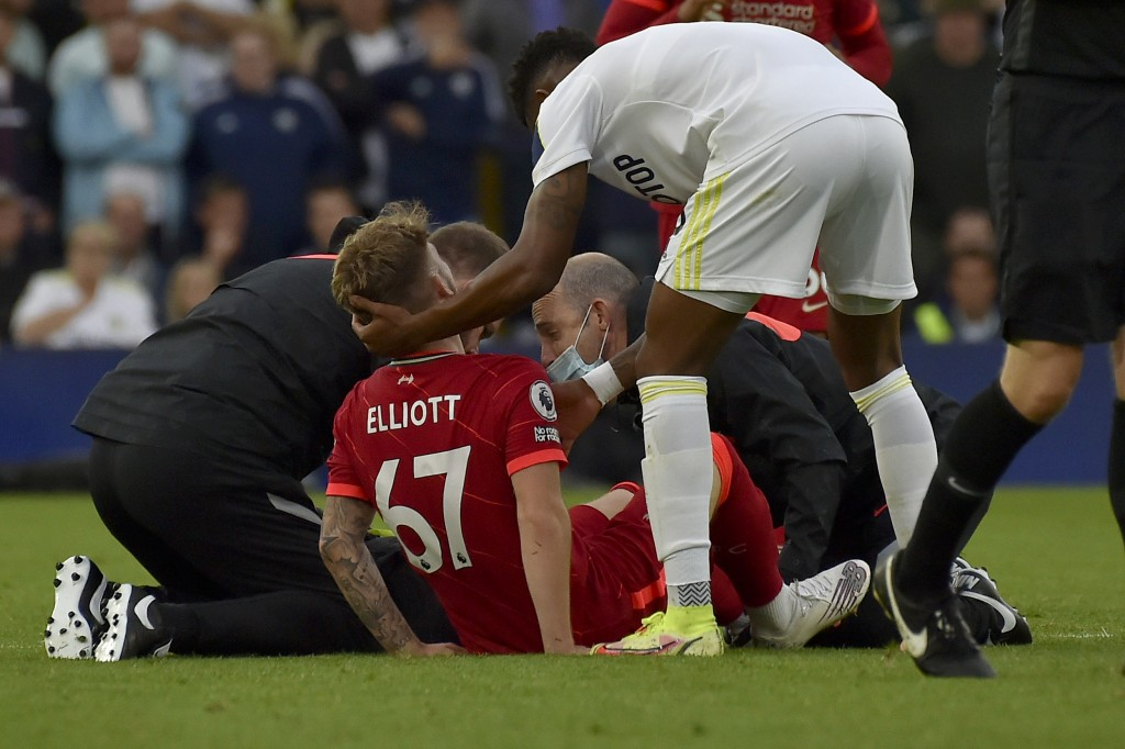 Leeds United's Junior Firpo holds the head of Liverpool's Harvey Elliott being assisted after he got injured in a clash with Leeds United's Pascal Str...