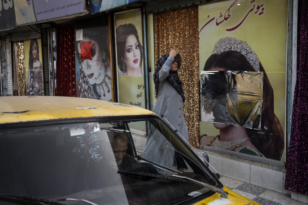 An Afghan woman walks past beauty salons with defaced window decorations, in Kabul, Afghanistan, Sunday, Sept. 12, 2021. Since the Taliban gained cont...