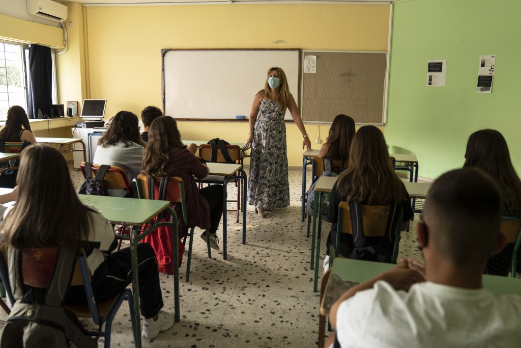 A teacher wearing a protective face mask speaks to her pupils in junior high school in Athens, Monday, Sept. 13, 2021. Public and private sector emplo...