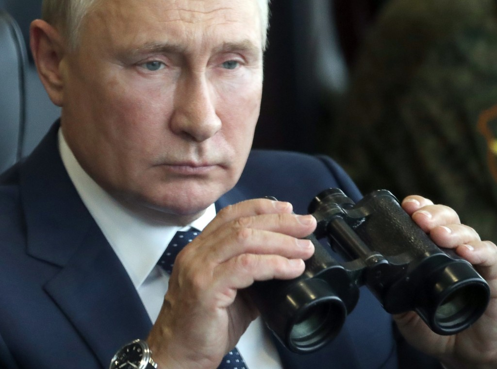 Russian President Vladimir Putin holds a binoculars as he watches the joint strategic exercise of the armed forces of the Russian Federation and the R...