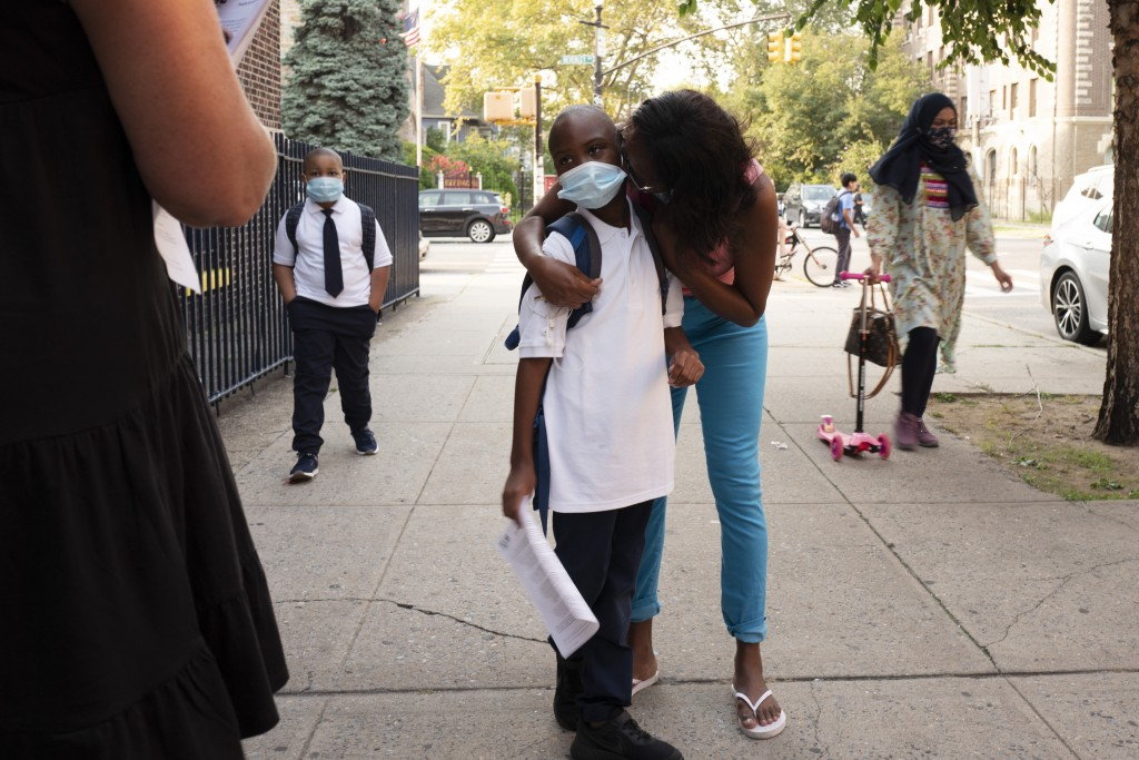 A mother kisses her son as he arrives for the first day of school at Brooklyn's PS 245, Monday, Sept. 13, 2021 in New York. Classroom doors are swingi...