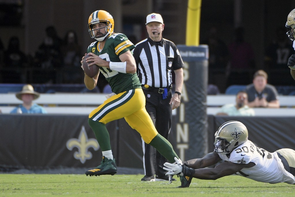 Green Bay Packers quarterback Aaron Rodgers, left, scrambles as he is pressured by New Orleans Saints linebacker Tanoh Kpassagnon during the first hal...