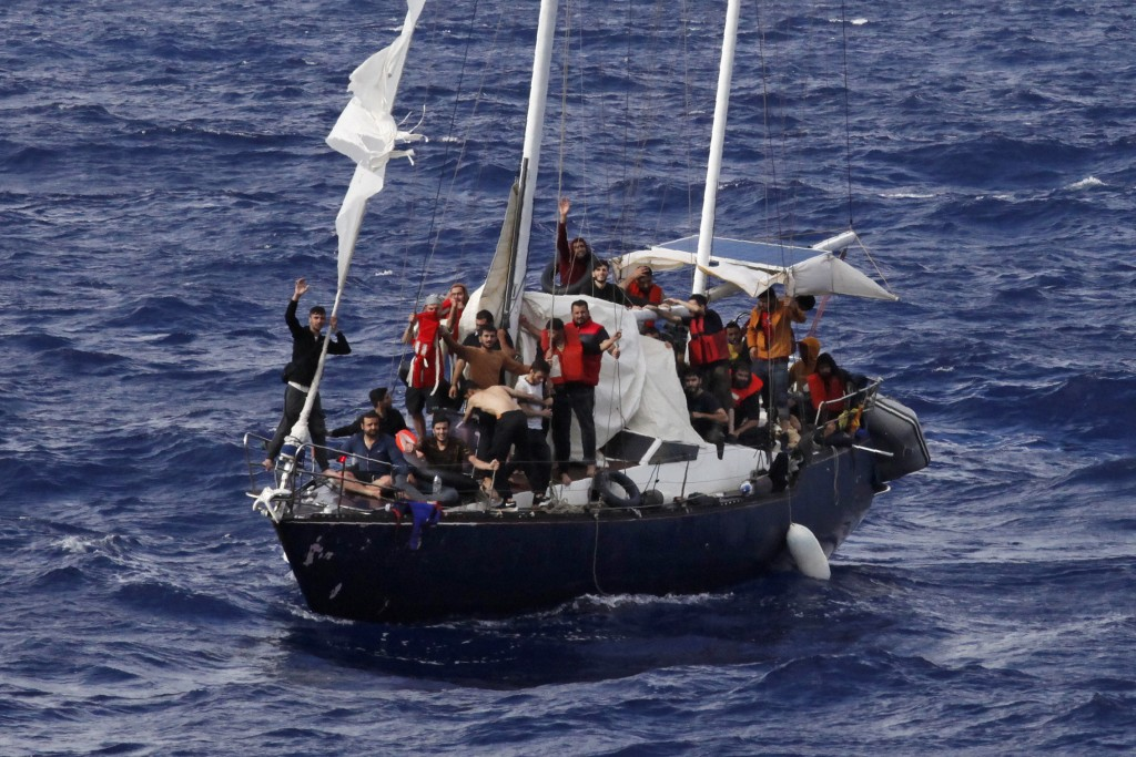 Migrants wave for help as they wait for the Italian coast guard to rescue them, on international waters in the Mediterranean Sea, Sunday, Sept. 12, 20...