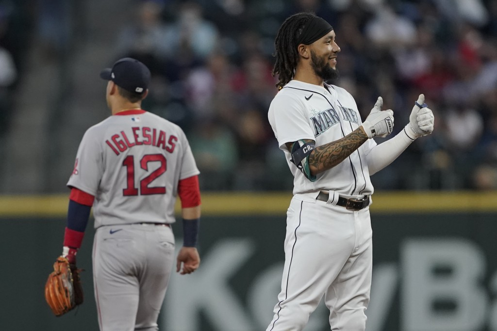 Seattle Mariners' J.P. Crawford, right, reacts next to Boston Red Sox second baseman Jose Iglesias (12) after Crawford hit a double, with fan interfer...