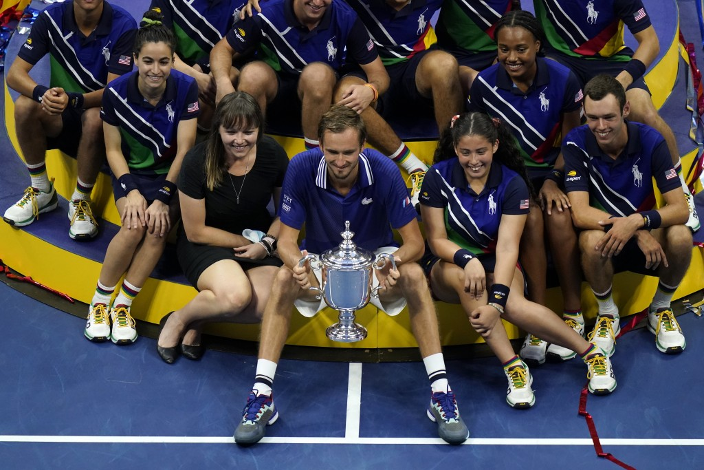Daniil Medvedev, of Russia, poses for photos with court attendants after defeating Novak Djokovic, of Serbia, in the men's singles final of the US Ope...