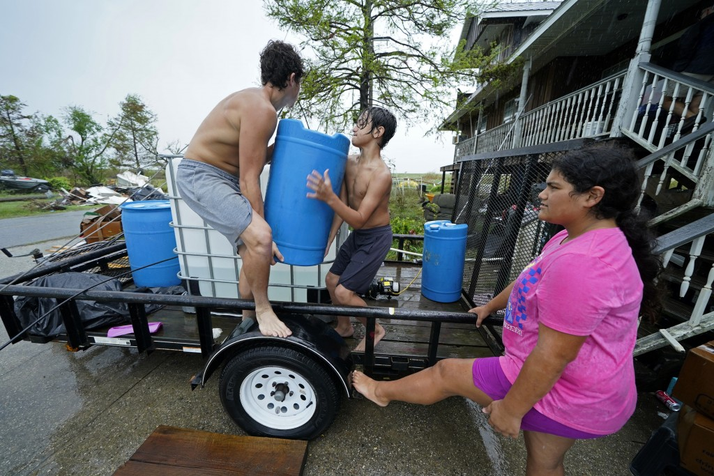 Terren Dardar, 17, left, Dayton Verdin, 14, and Lerryn Brune, 10, move barrels of rainwater they collected from Tropical Storm Nicholas, in the afterm...