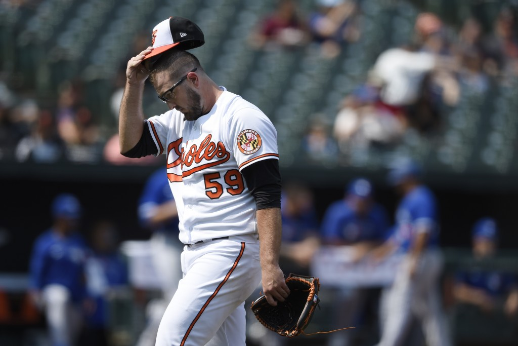 Baltimore Orioles starting pitcher Zac Lowther walks to the dugout after giving up five runs to the Toronto Blue Jays in the first inning of a basebal...