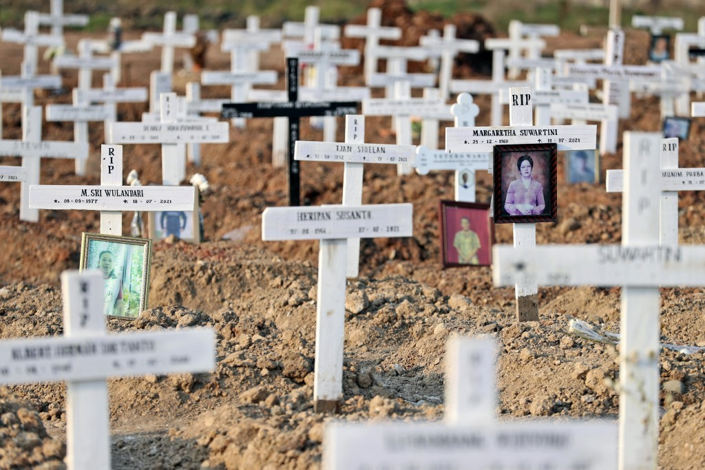 Portraits are left on the graves of those who died of COVID-19 at Rorotan Cemetery in Jakarta, Indonesia, Wednesday, Aug. 25, 2021. In the graveyard o...