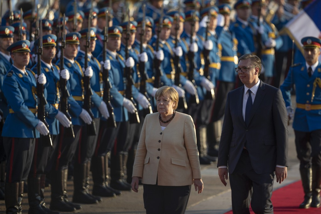 German Chancellor Angela Merkel, center, walks past honor guards while being accompanied by Serbia's president Aleksandar Vucic, front right, in Belgr...