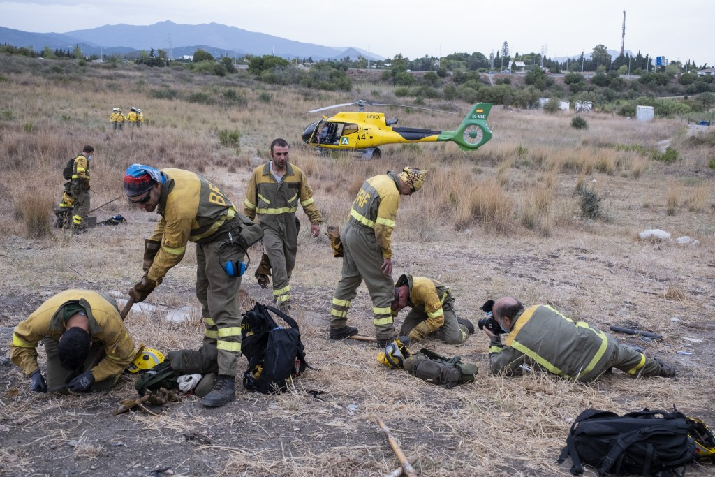 Forest firefighters prepare their equipment before boarding the helicopter to work on extinguishing a wildfire near the town of Jubrique, in Malaga pr...