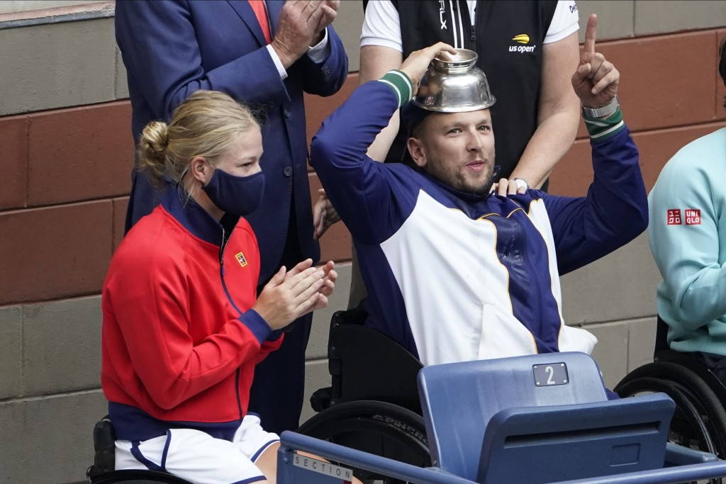 Diede De Groot, of the Netherlands, left, and Dylan Alcott, of Australia react to the crowd while watching play between Novak Djokovic, of Serbia, and...