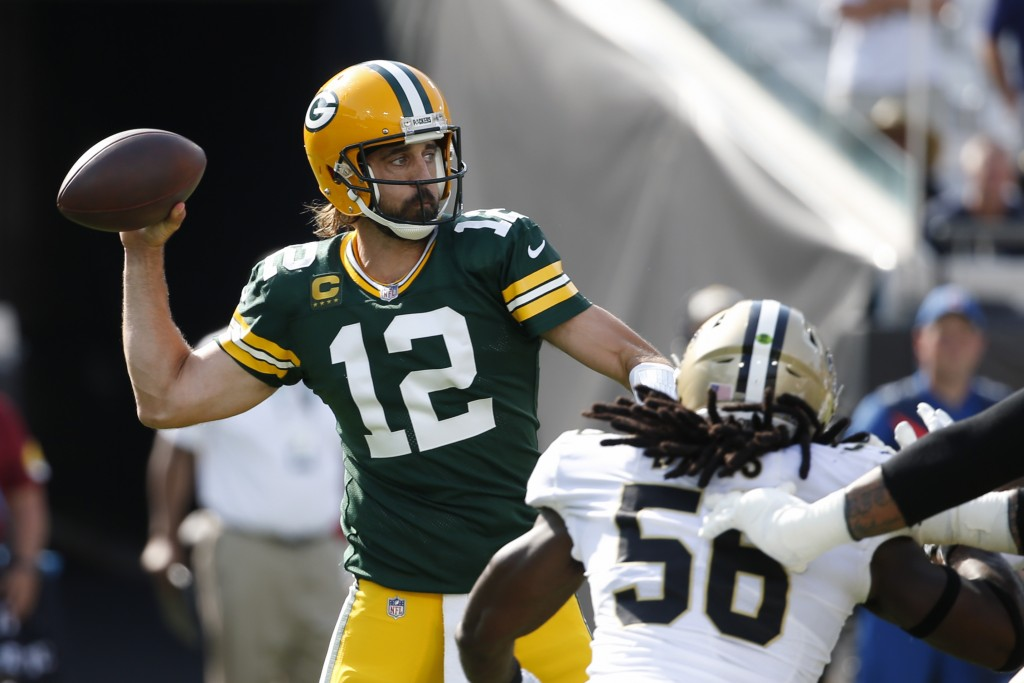 Green Bay Packers quarterback Aaron Rodgers (12) throws a pass as New Orleans Saints outside linebacker Demario Davis (56) rushes during the first hal...