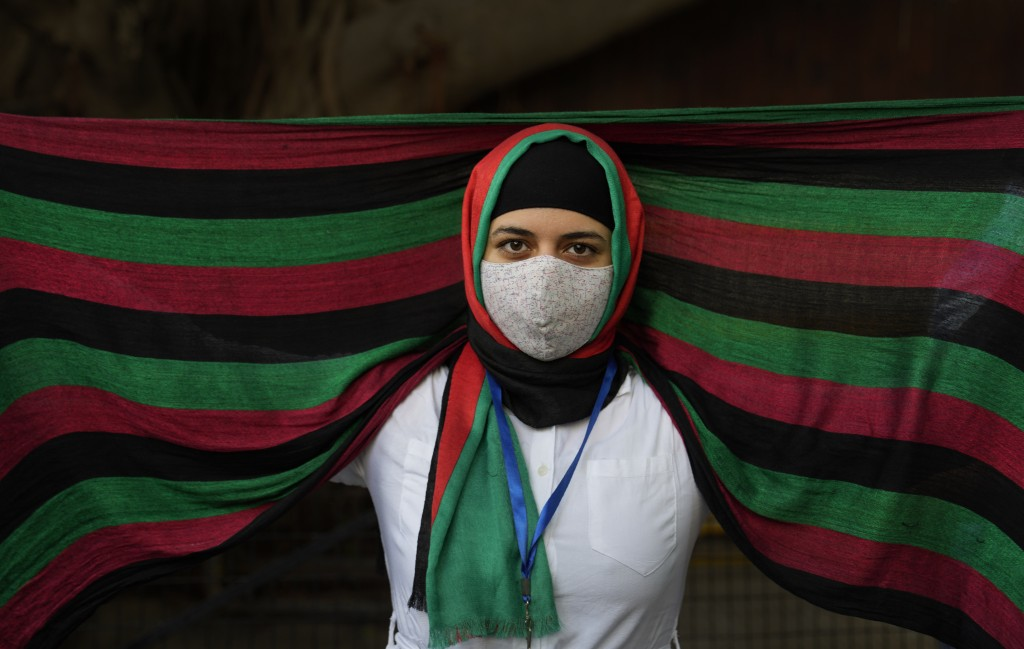 FILE - In this Aug. 23, 2021, file photo, an Afghan refugee living in India wearing a scarf in the colors of Afghanistan flag participates in a protes...