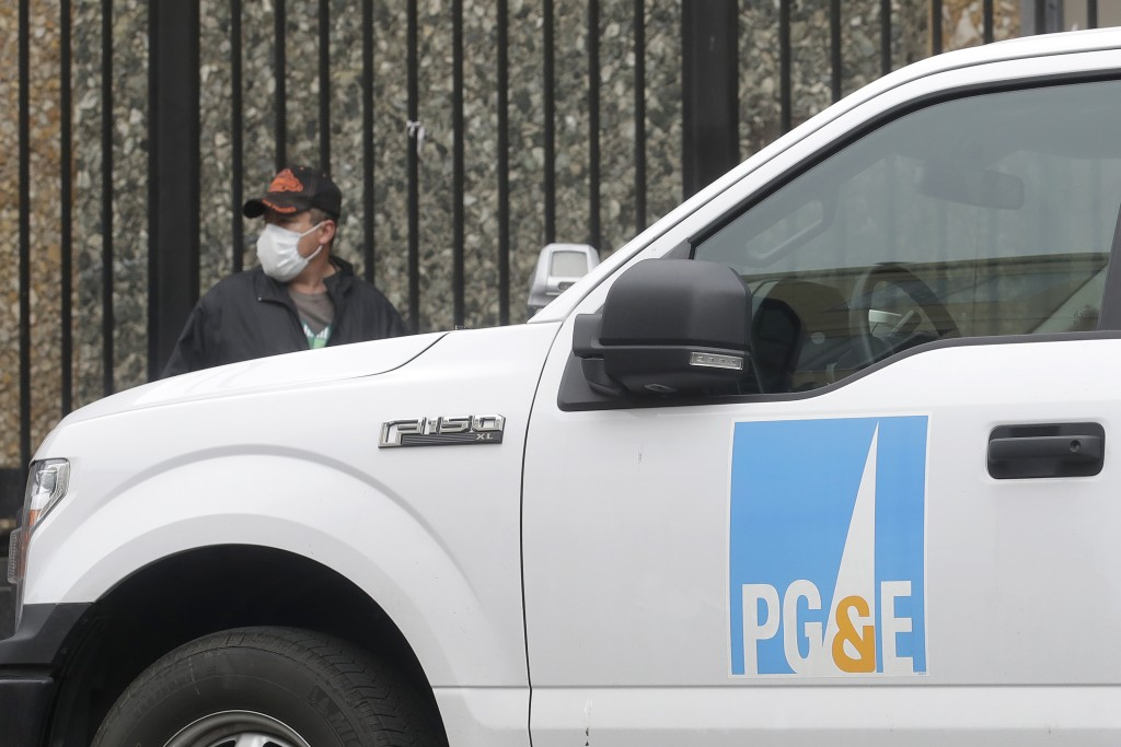 FILE - In this April 16, 2020, file photo, a man wearing a mask walks behind a Pacific Gas and Electric truck in San Francisco. A Pacific Gas & Electr...