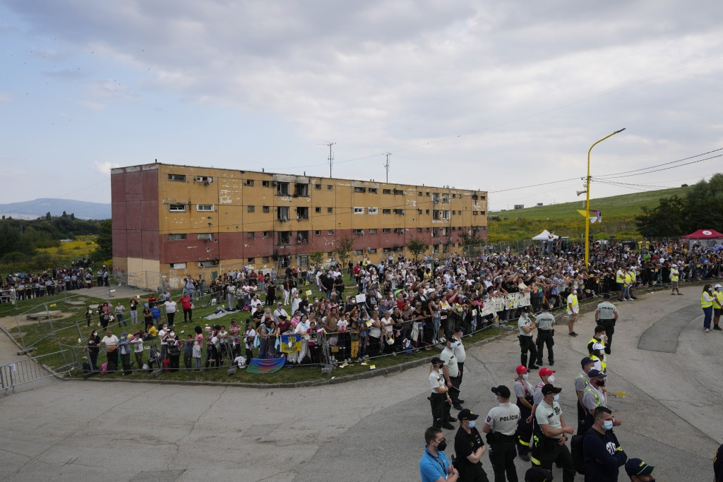 Residents watch Pope Francis meeting with members of the Roma community at Lunik IX, in Kosice, Slovakia, Tuesday, Sept. 14, 2021, the biggest of abou...