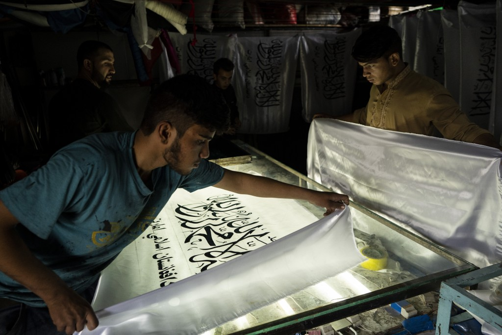 Workers hand-print Taliban flags in a small workshop in Kabul's Jawid market, Afghanistan, Sunday, Sept. 12, 2021. The flag shop, tucked away in the c...