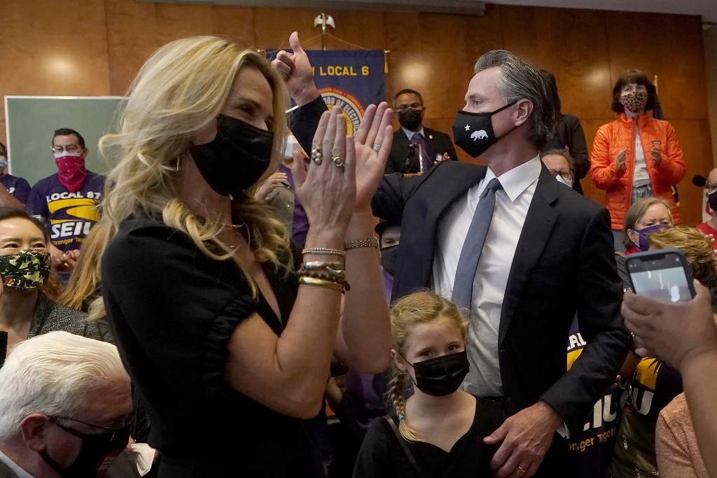 Gov. Gavin Newsom, middle right, gestures next to his wife, Jennifer Siebel Newsom, foreground, and their daughter, Brooklynn, bottom, after speaking ...