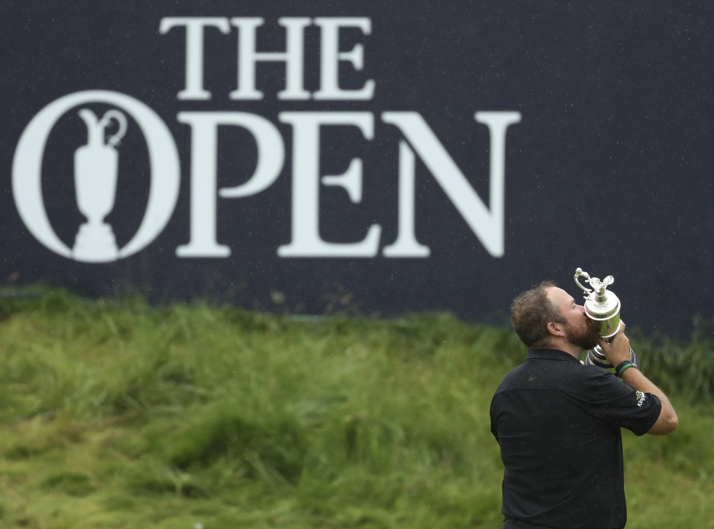 FILE - In this Sunday, July 21, 2019 file photo, Ireland's Shane Lowry holds and kisses the Claret Jug trophy on the 18th green as he poses for the cr...