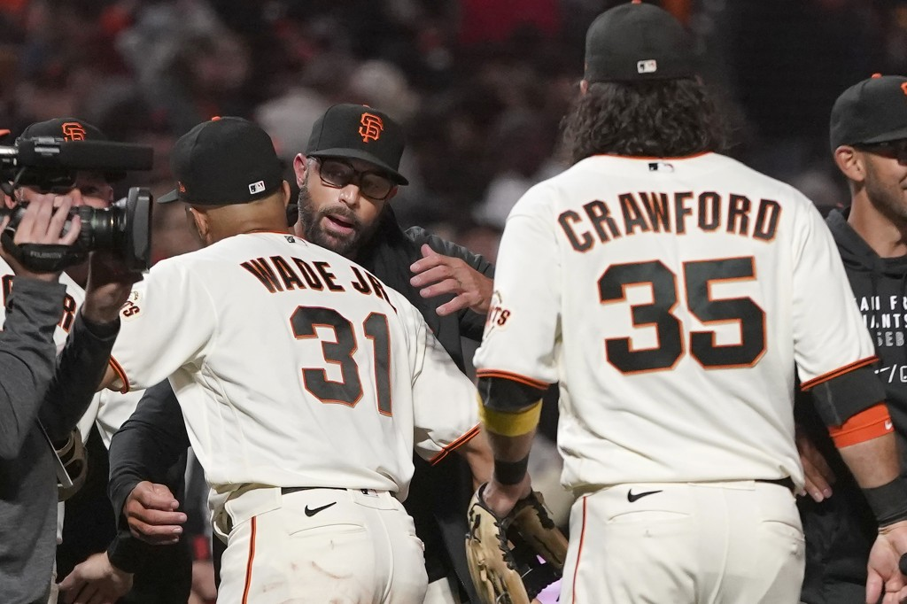 San Francisco Giants manager Gabe Kapler, middle, celebrates with LaMonte Wade Jr. (31) and Brandon Crawford (35) after the Giants defeated the San Di...