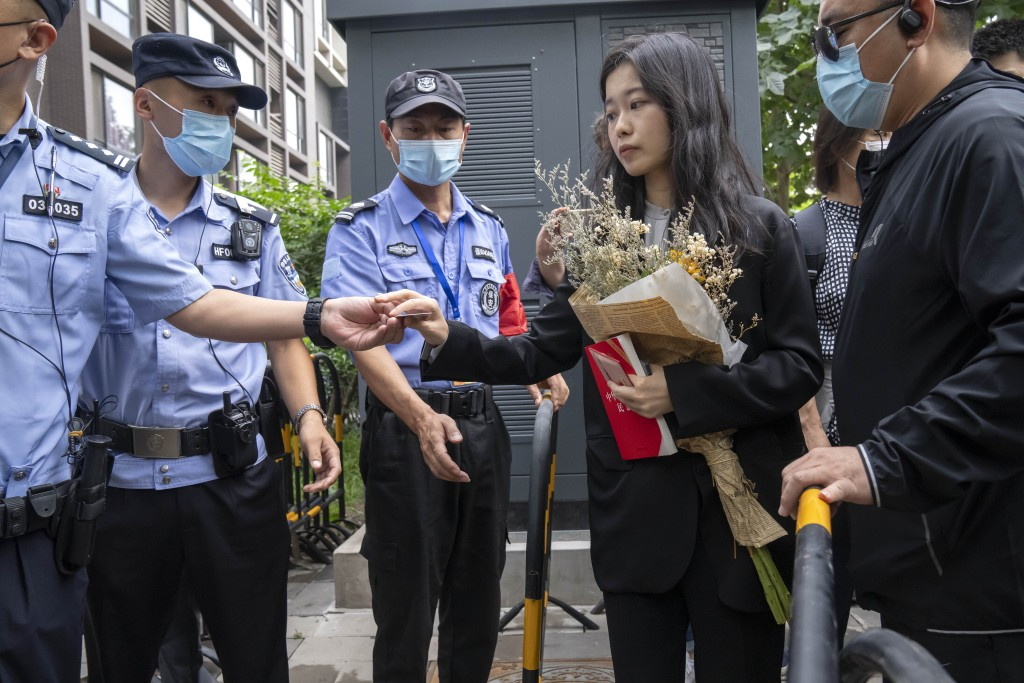 Zhou Xiaoxuan, a former intern at China's state broadcaster CCTV, has her identification checked at a barricade outside a courthouse in Beijing, Tuesd...