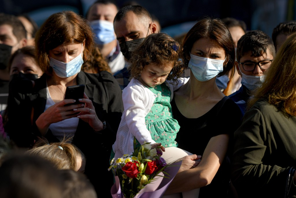 A woman wearing a face mask holds a little girl during festivities marking the beginning of the school year at a school in Bucharest, Romania, Monday,...