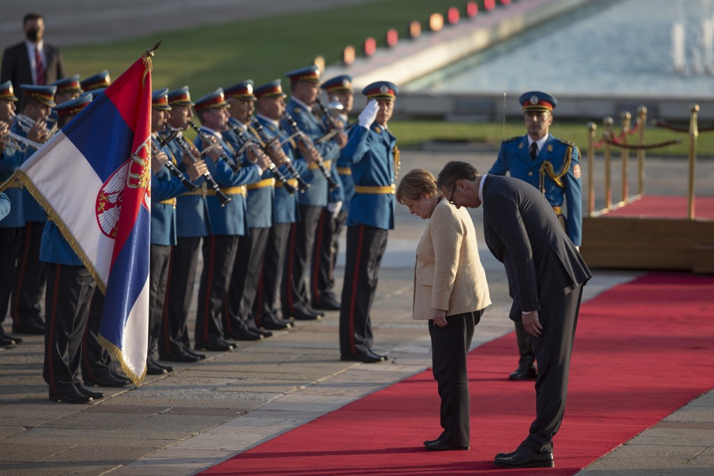 German Chancellor Angela Merkel, center, bows to the Serbian flag while being accompanied by Serbia's president Aleksandar Vucic, front right, in Belg...