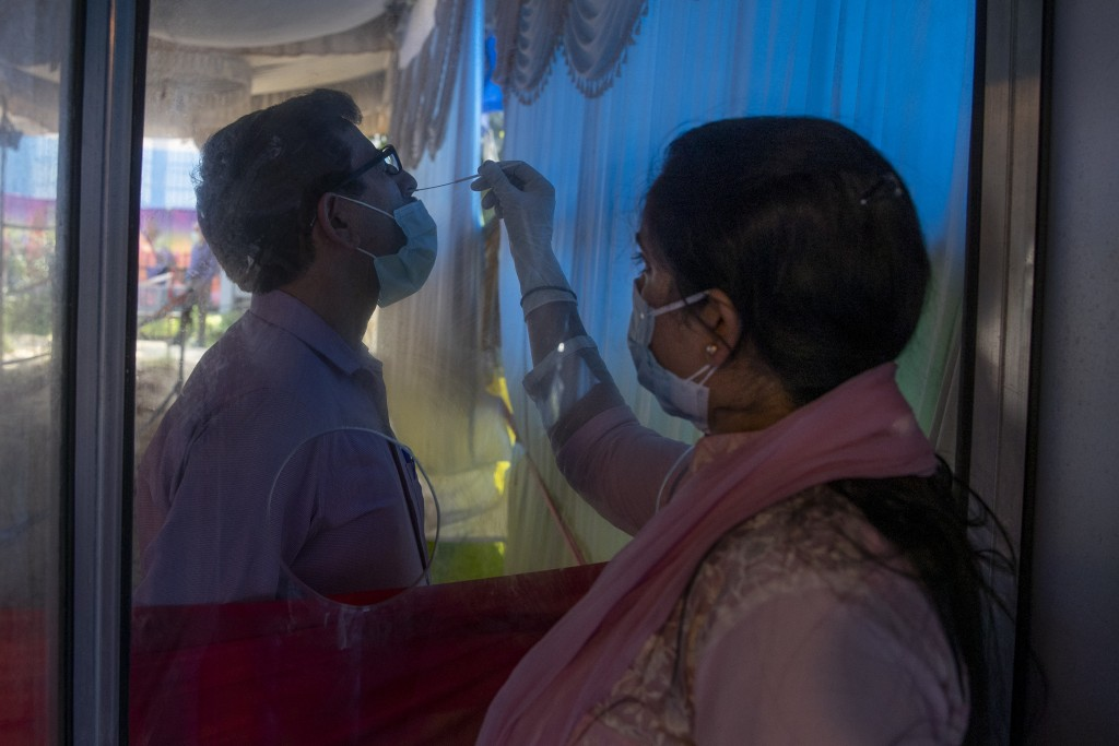 A health worker takes a nasal swab sample of a man to test for COVID-19 in Srinagar, Indian controlled Kashmir, Tuesday, Sept.14, 2021. (AP Photo/ Dar...