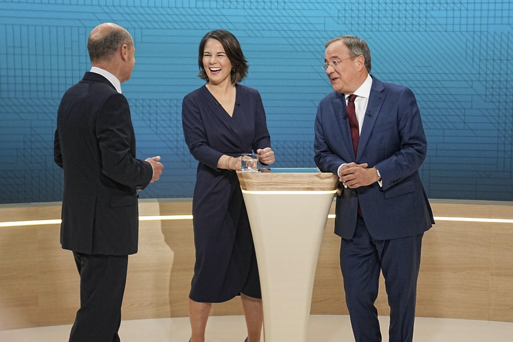 From left, Chancellor candidates Olaf Scholz (SPD), Annalena Baerbock (Green Party) and Armin Laschet (CDU) stand in the TV studio in Berlin, Sunday, ...