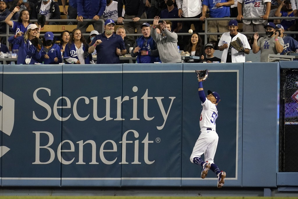 Los Angeles Dodgers right fielder Mookie Betts makes a leaping catch on a pop fly by Arizona Diamondbacks' Christian Walker during the sixth inning of...