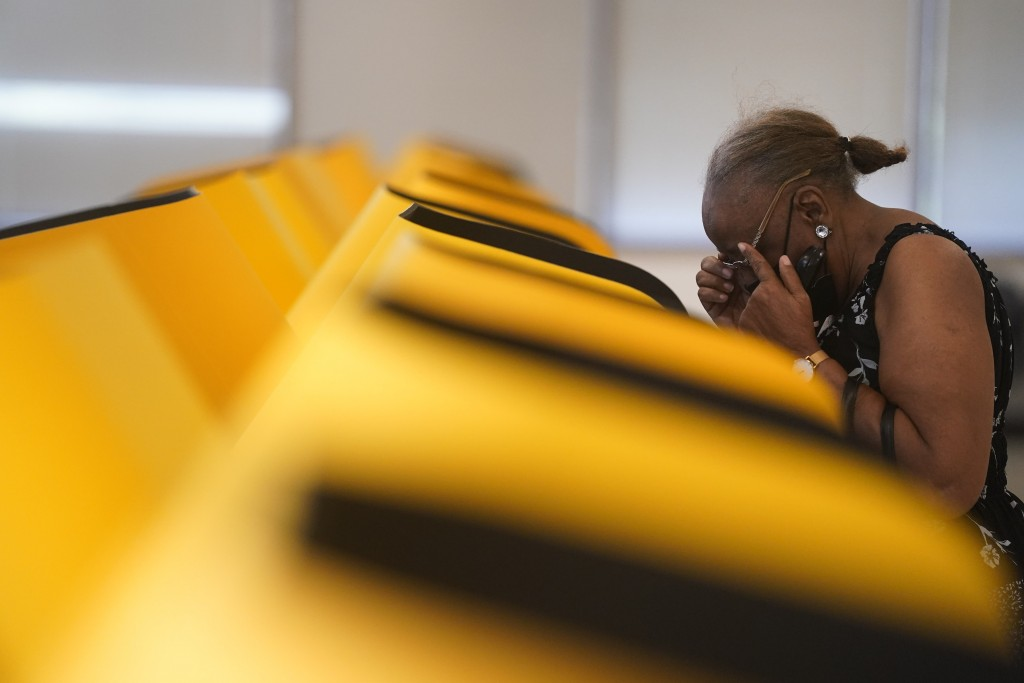FILE — In this Sept. 7, 2021 file photo Jacqueline Magee adjusts her reading glasses while casting an early ballot for the California gubernatorial re...