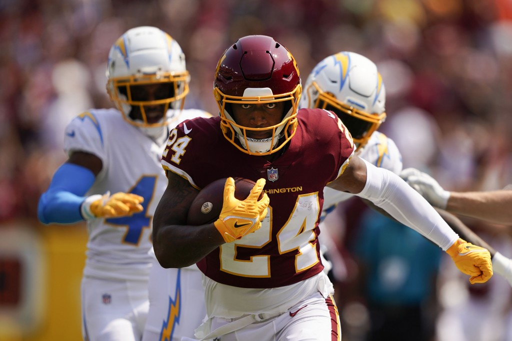 Washington Football Team running back Antonio Gibson (24) runs with the ball against the Los Angeles Chargers during the first half of an NFL football...